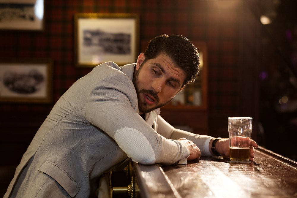 A man looking behind him in a bar.   Photo: Shutterstock