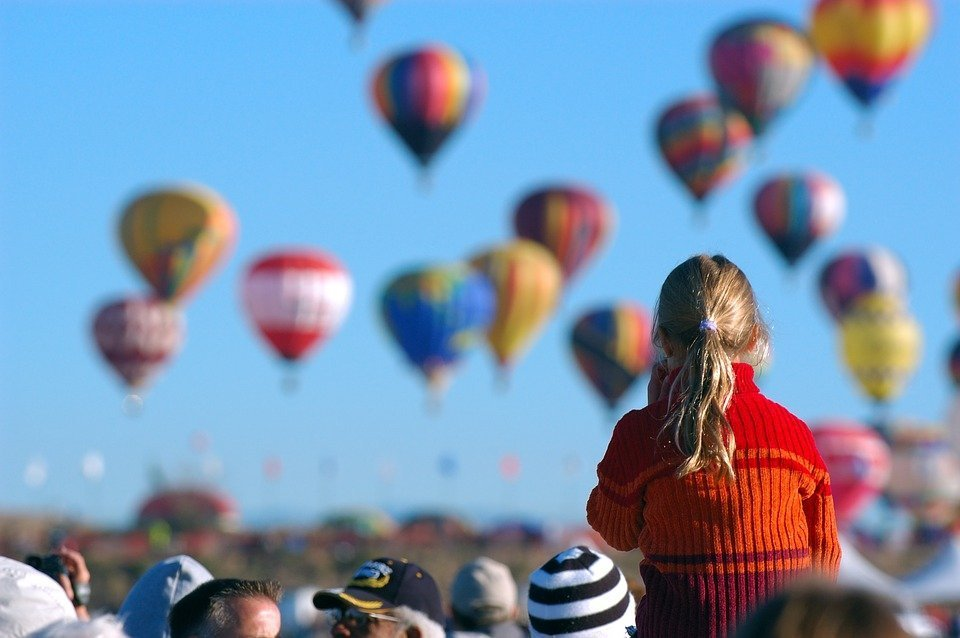 A little girl at an outdoor party looking at hot air balloons | Photo: Pixabay