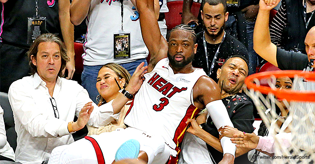 Dwyane Wade Gracefully Crashes into John Legend and Chrissy Teigen at Heat Game in Hilarious Photo