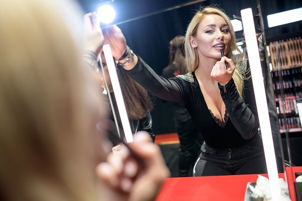 A woman poses with a lipstick during the Sephora store opening at Galeria Kaufhof | Photo: Getty Images
