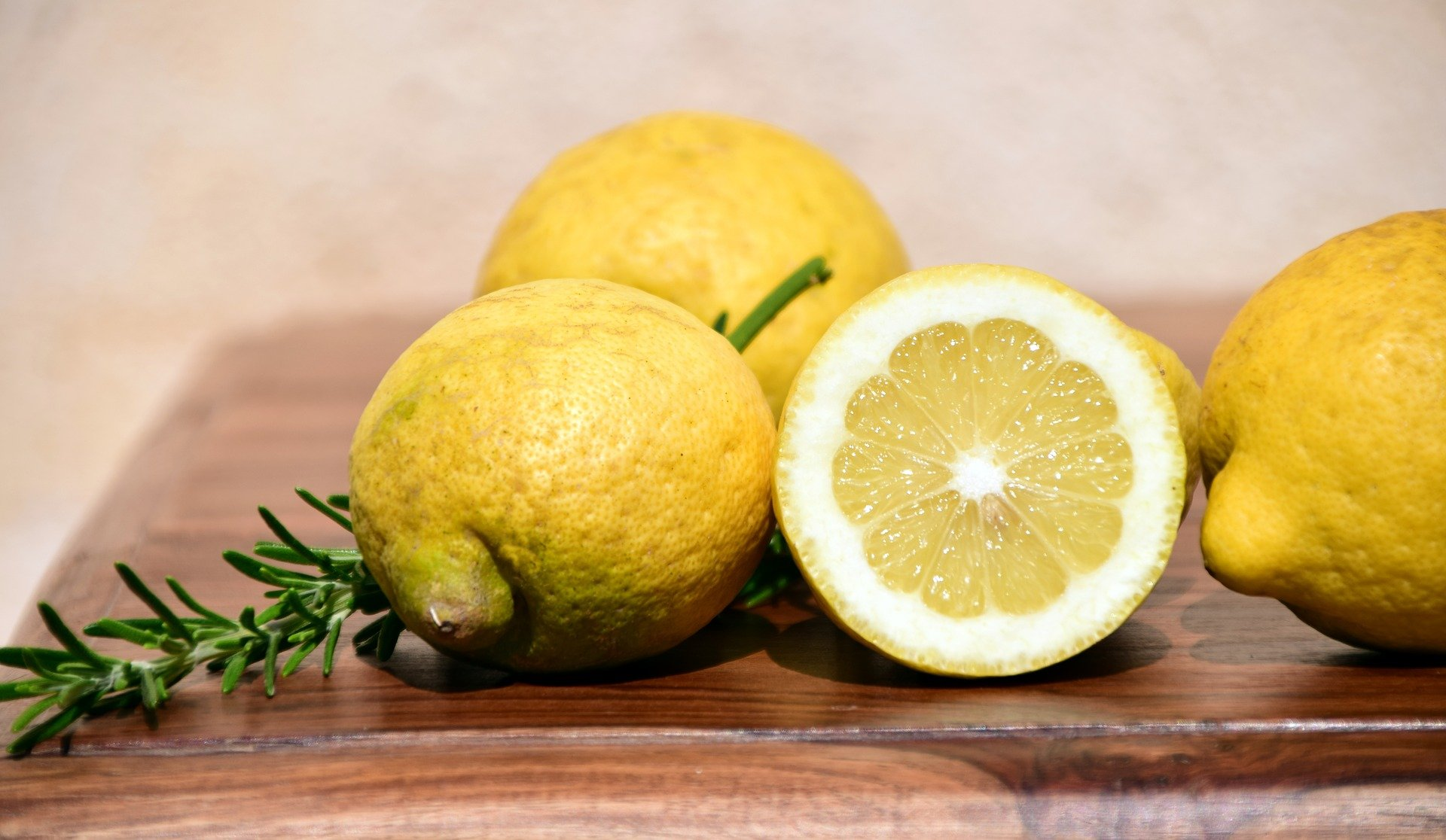Some lemons with a sprig of rosemary on a chopping board | Photo: Pixabay/Ulrike Leone
