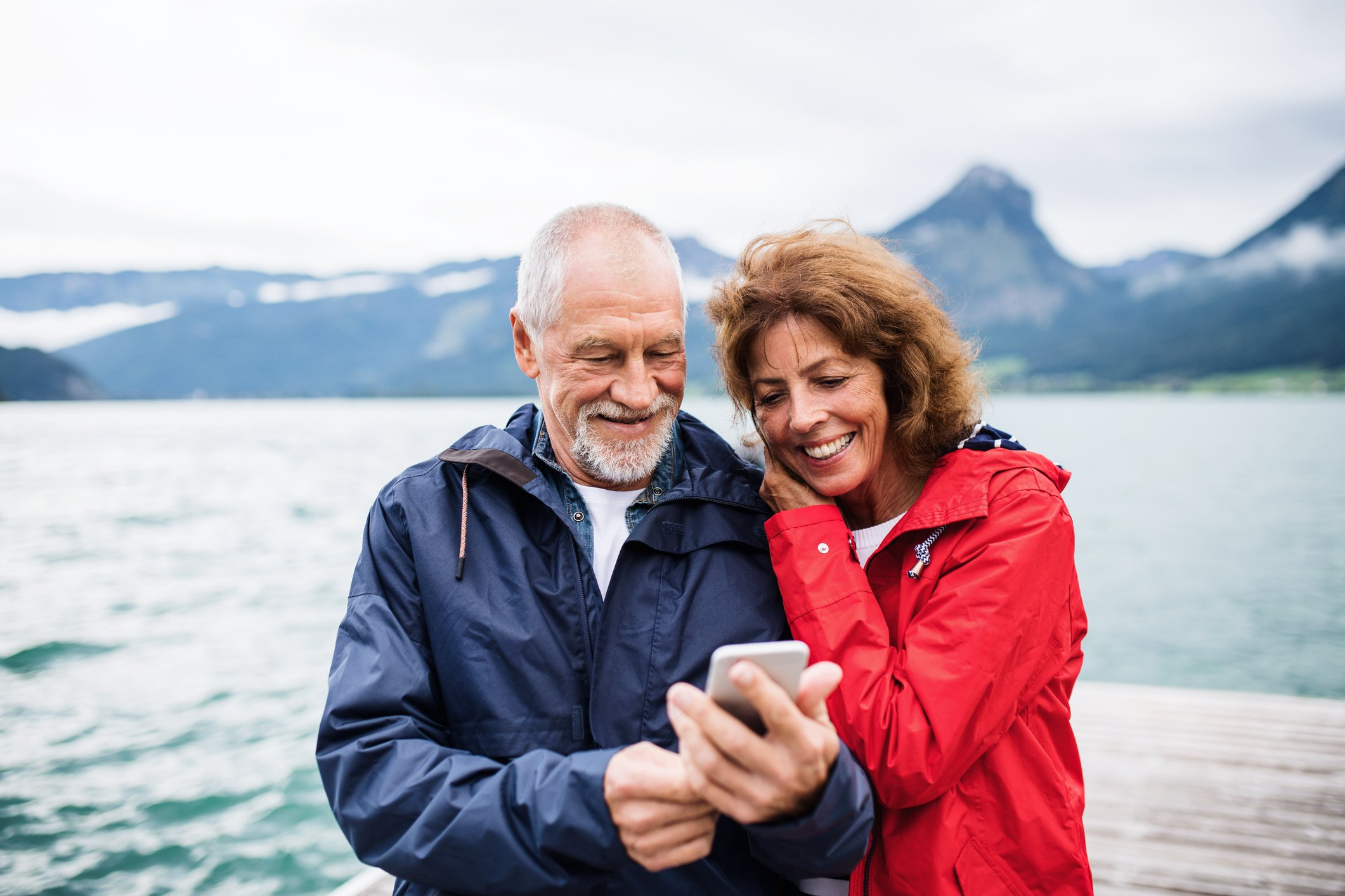 Un couple au bord d'un lac regardant un smartphone. | Photo : Getty Images