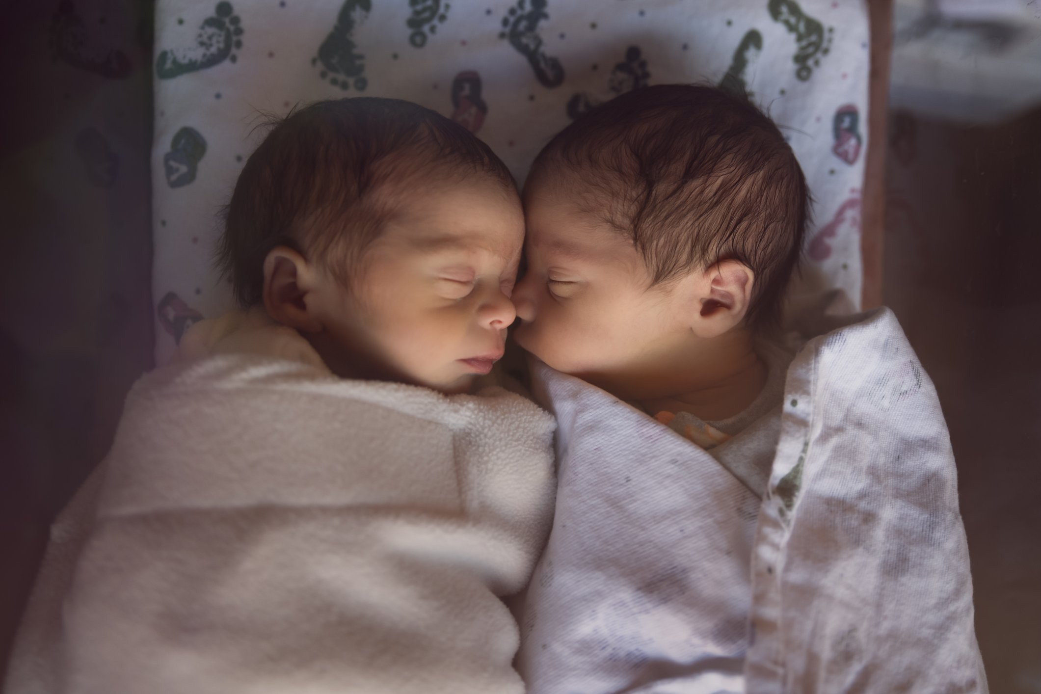 Premature Newborn Fraternal Twins in Hospital Sleep Together in Plastic Crib | Photo: Getty Images