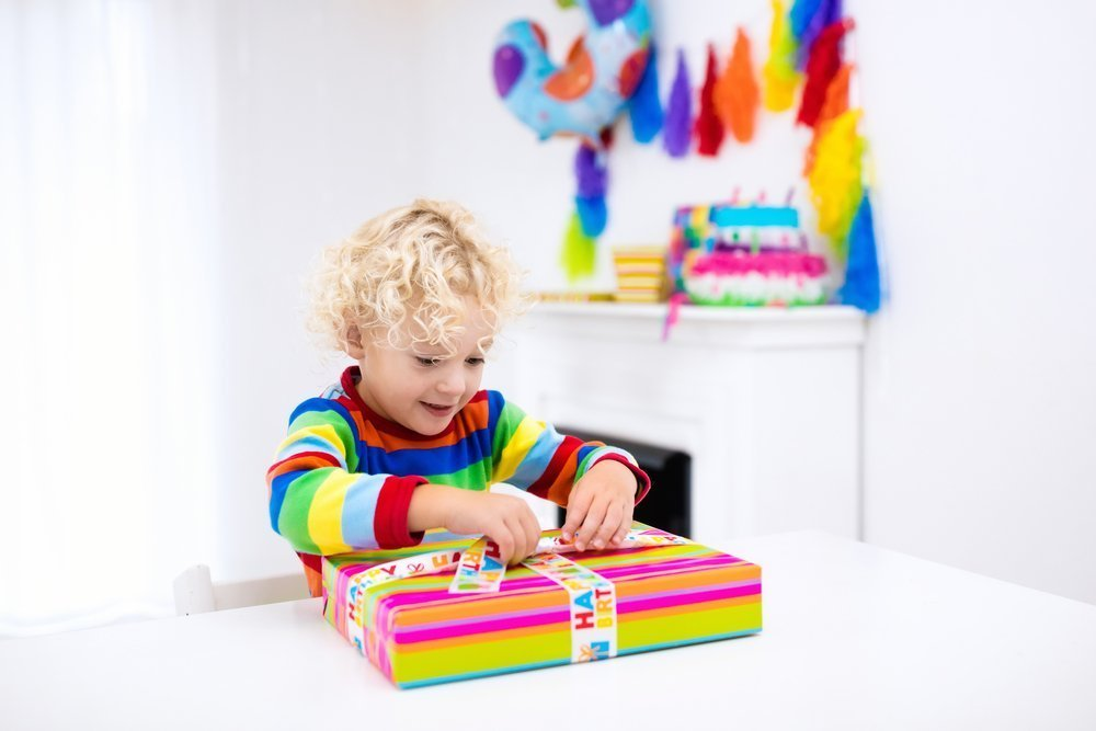 A young boy opening his birthday presents. | Photo: Shutterstock