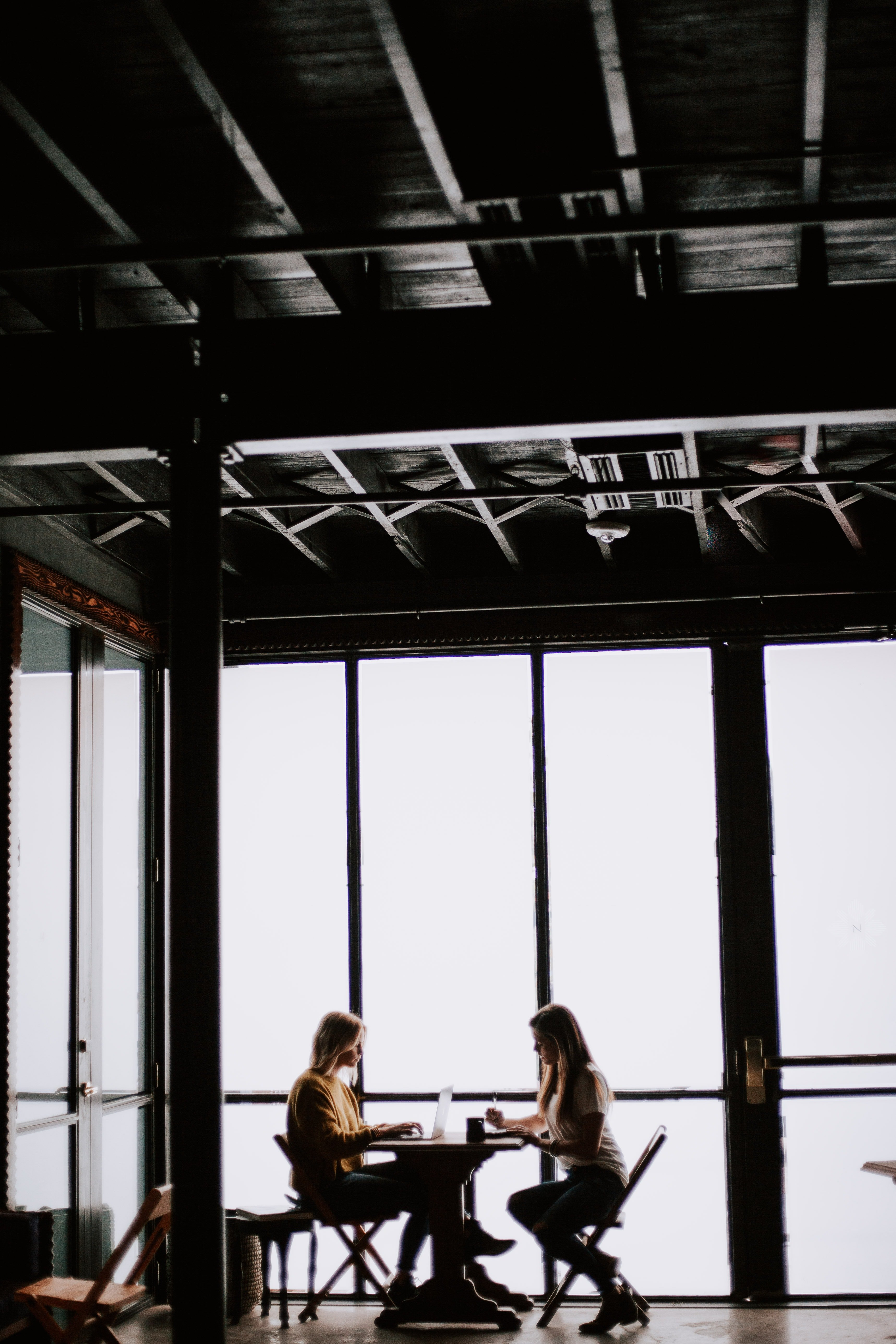 Two young women talking in a café | Photo: Unsplash