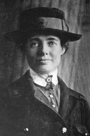 Black-and-white photograph of a white woman, Florence Merriam Johnson, wearing a hat and coat over a nurse's uniform, from 1921.| WikiCommons