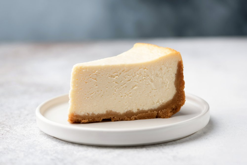 A photo of a slice of cheesecake on a white plate. | Photo: Shutterstock