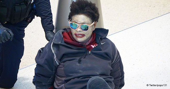 Woman wearing white face paint and sunglasses at airport shouts obscenities, police handcuff her