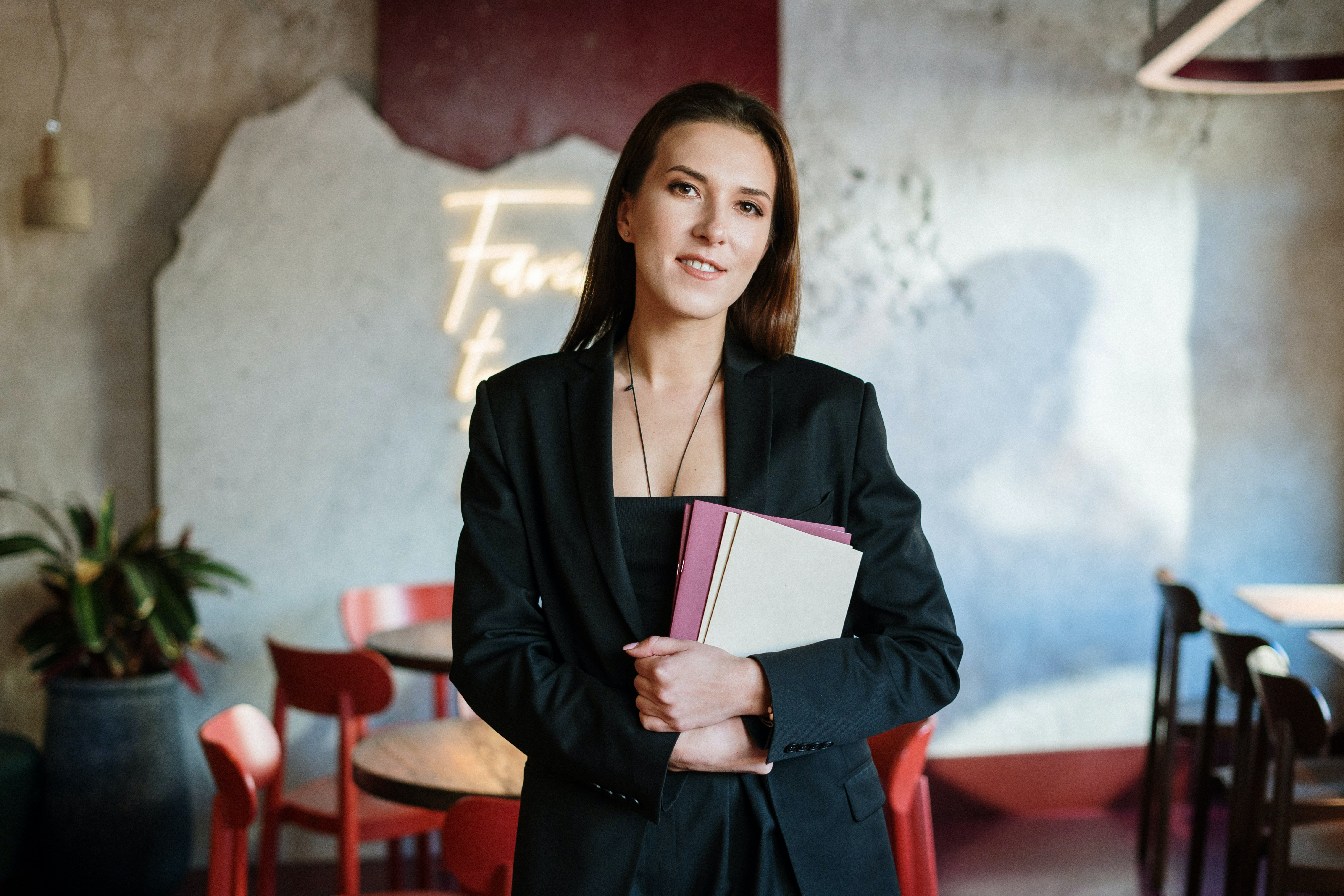 Woman in black blazer holding papers | Photo: Pexels