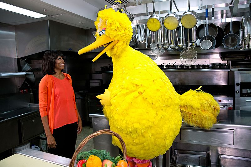 Caroll Spinney as Big Bird with former First Lady of the U.S. Michelle Obama during the third anniversary celebration of the Let's Move! initiative | Photo: Wikimedia Commons