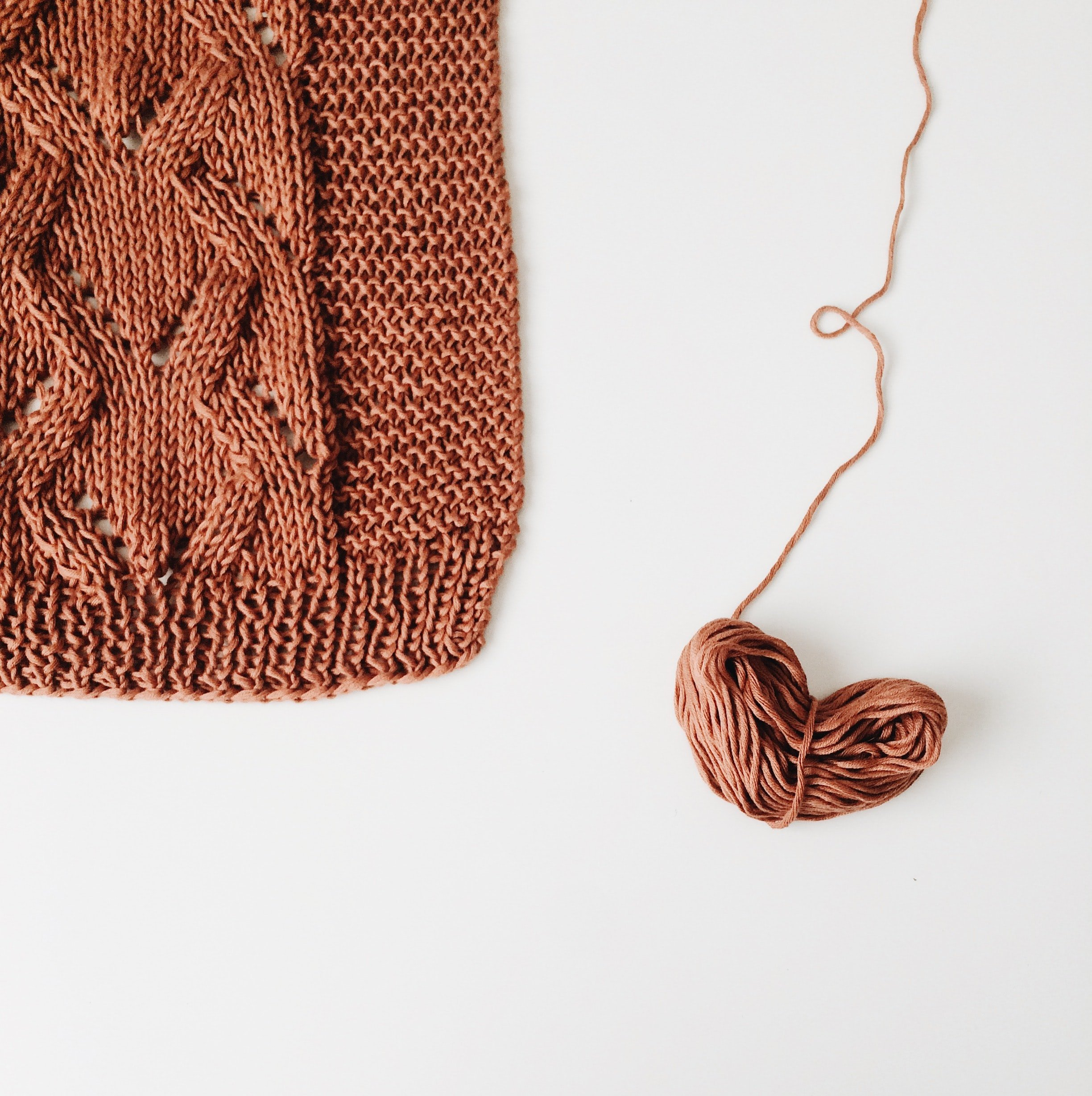 A ball of brown yarn and a portion of a brown knitted sweater | Source: Unsplash