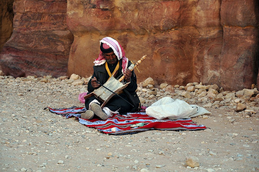 Jordanian bedouin man sit on a blanket in front of a mountain while playing a musical instrument on April 8 2010, in Petra, Jordan | Source Getty Images