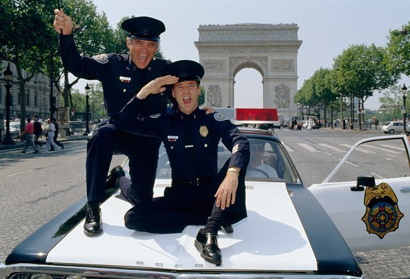 G.W. Bailey and Lance Kinsey ride on a police car down the Champs-Elysees | Photo: Getty Images
