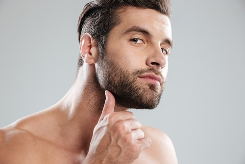 A young man examining his beard. | Source: Shutterstock.