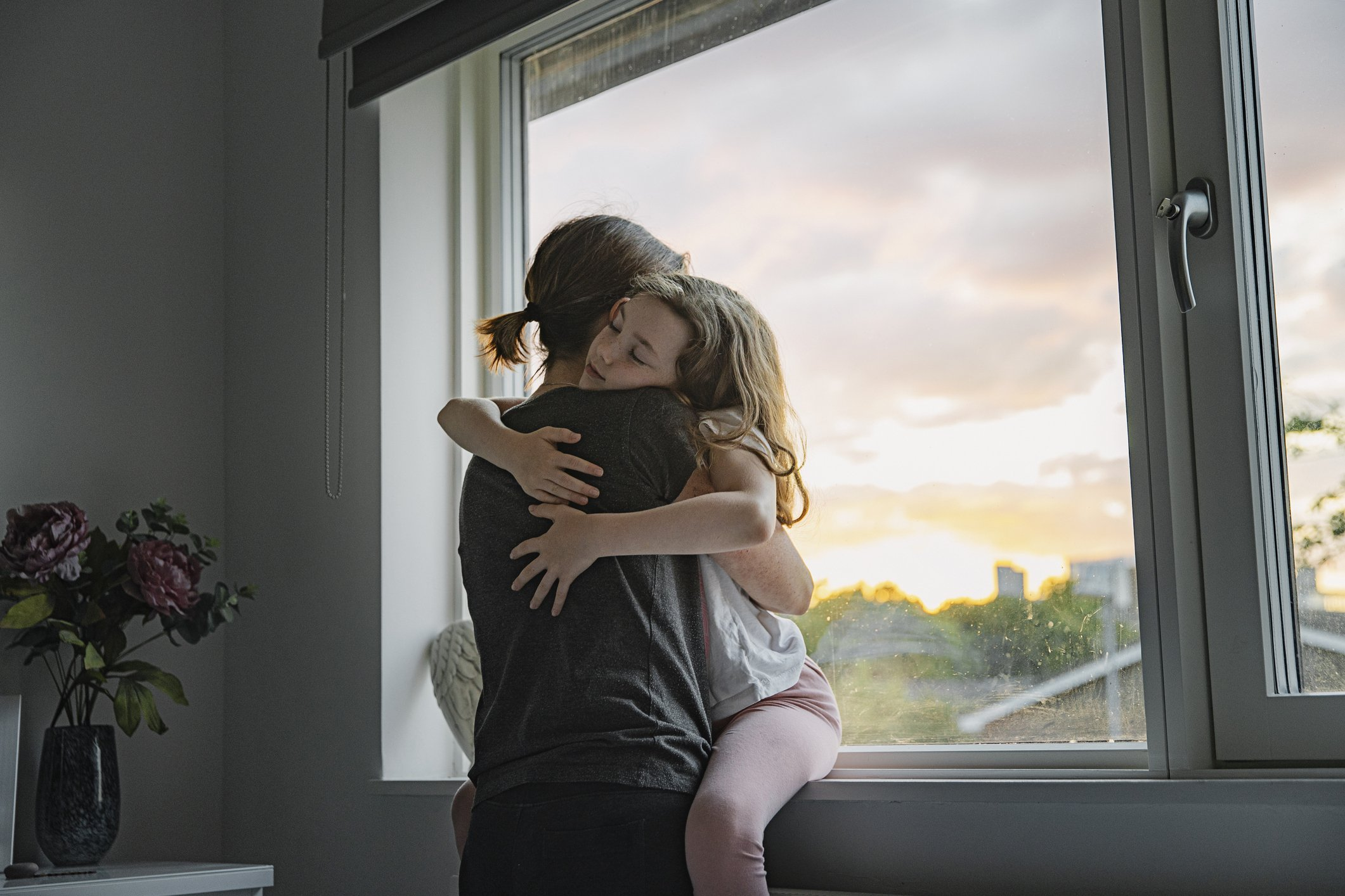 Young girl getting a big cuddle from her mother.   Photo: Getty Images