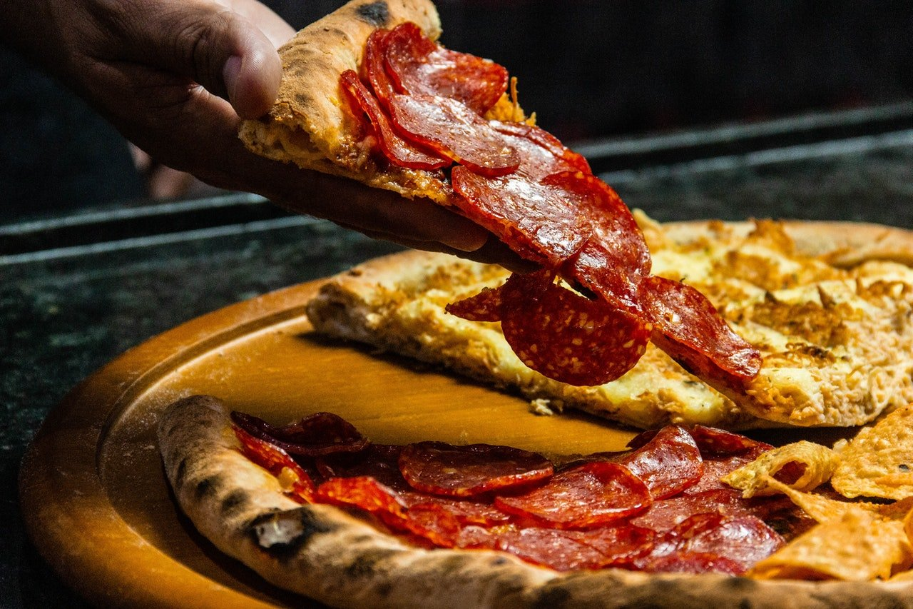 Photo of a hand holding a slice of pizza | Photo: Pexels