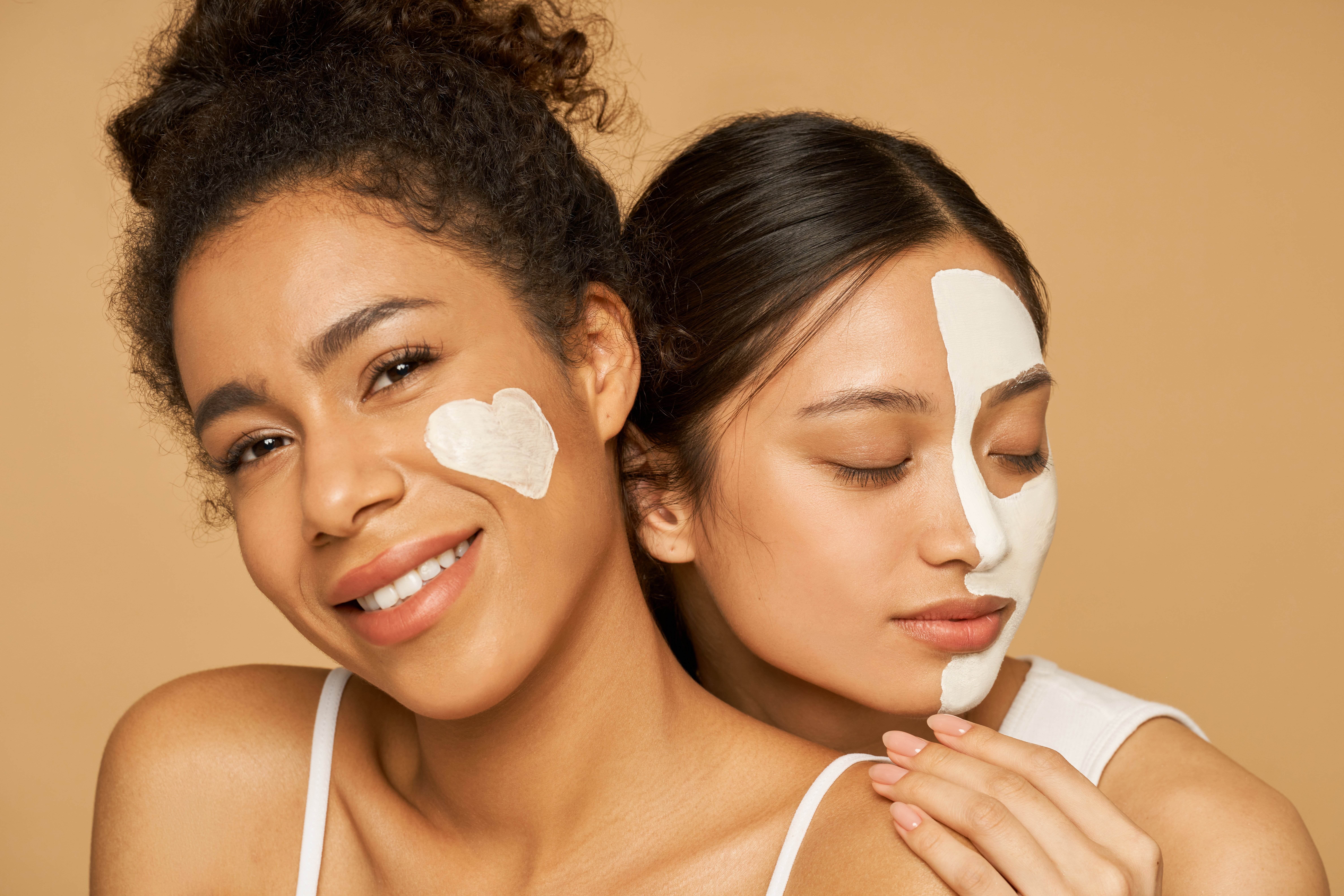 Women with lotion on their faces | Shutterstock