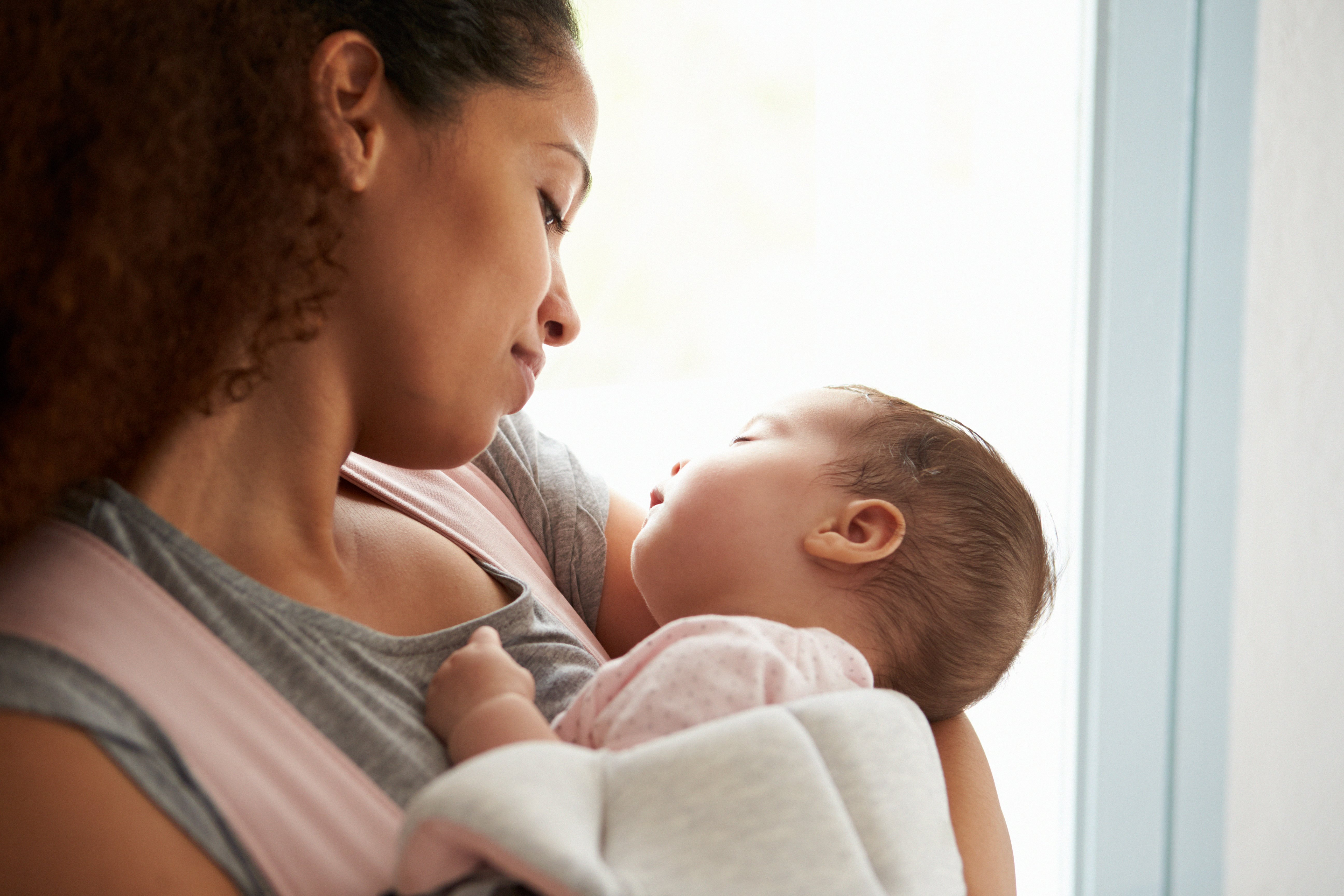 A woman holds a baby to her chest | Photo: Shutterstock
