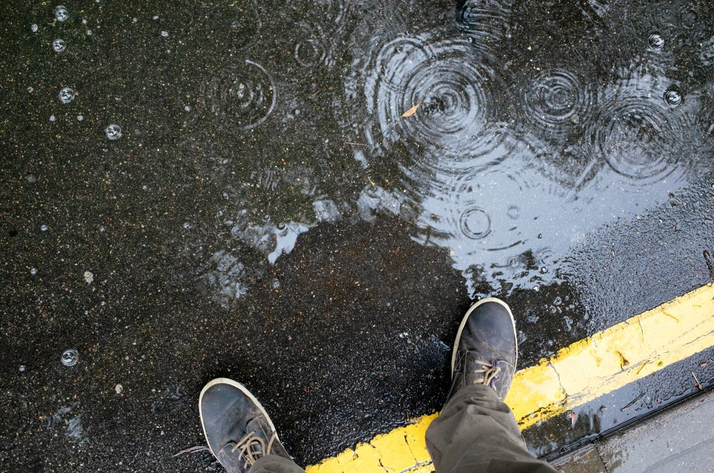 Man standing in rainwater puddle on a sidewalk | Photo: Shutterstock/IU Liquid and water photo