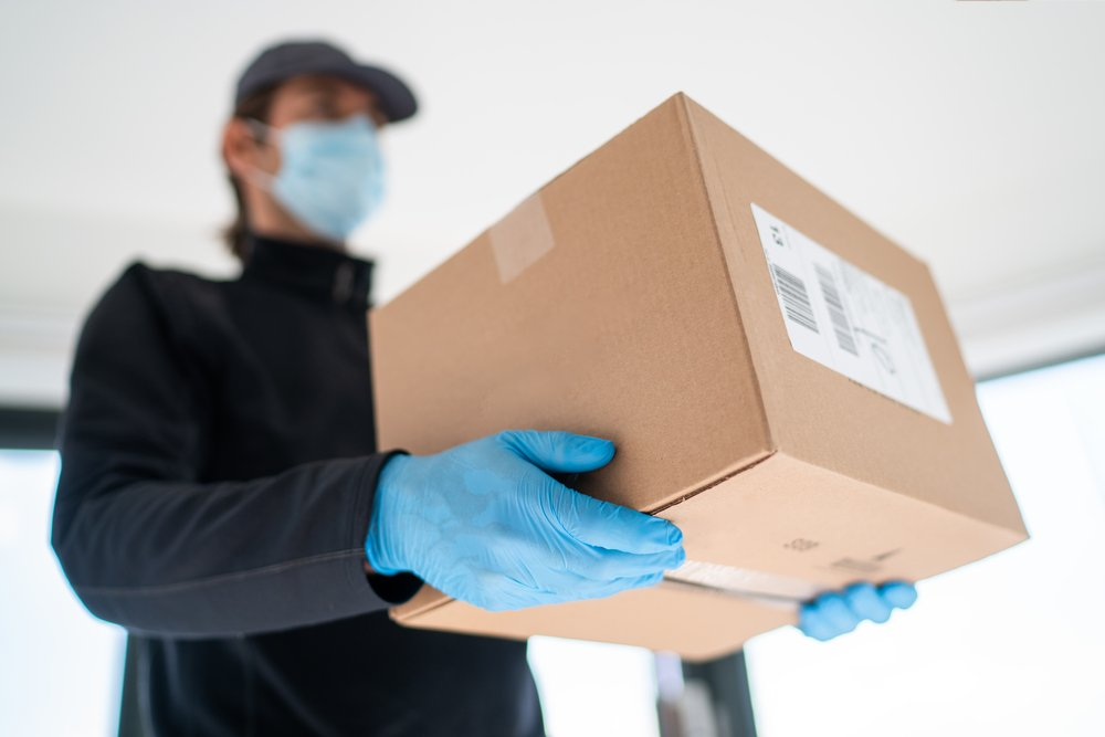 A photo of a delivery man carrying a box | Photo: Shutterstock