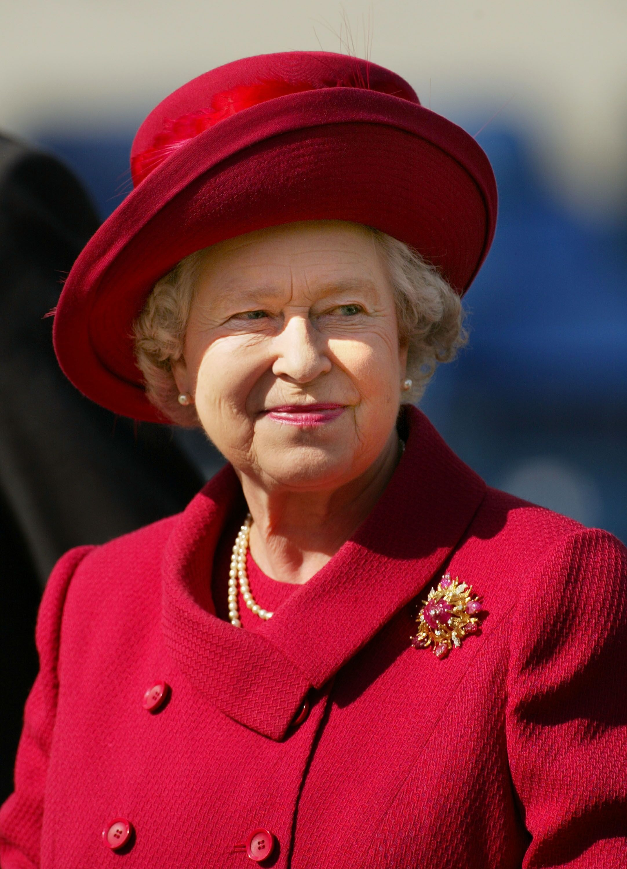"Queen Elizabeth smiles May 18, 2002 after presenting a trophy for the ""best turned out trooper"" to a Household Cavalry soldier at The Royal Windsor Horse Show at Windsor Great Park, England. 