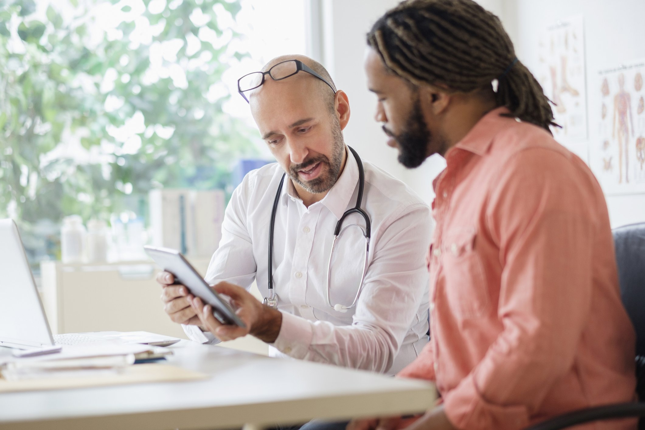 Doctor giving consultation to patient using digital tablet | Photo: Getty Images
