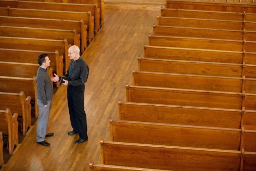 Priest pictured talking with man in church | Photo: Getty Images