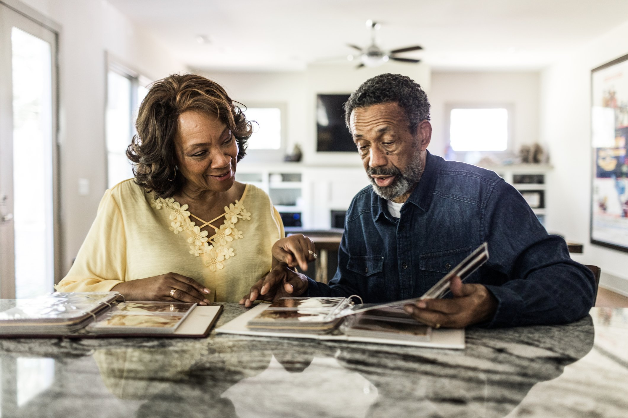 Senior couple looking through photo album at home|Photo: Getty Images