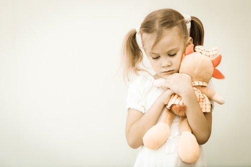Niña abranzando su peluche| Imagen: Shutterstock