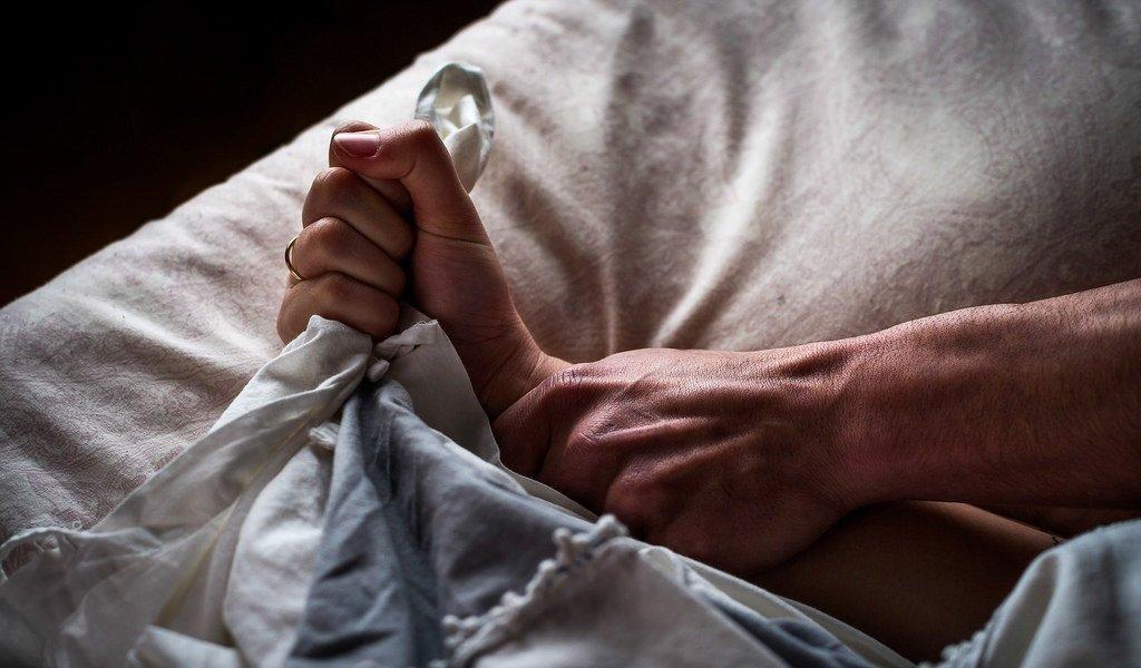 Mann hält Frau im Bett nieder | Quelle: Flickr