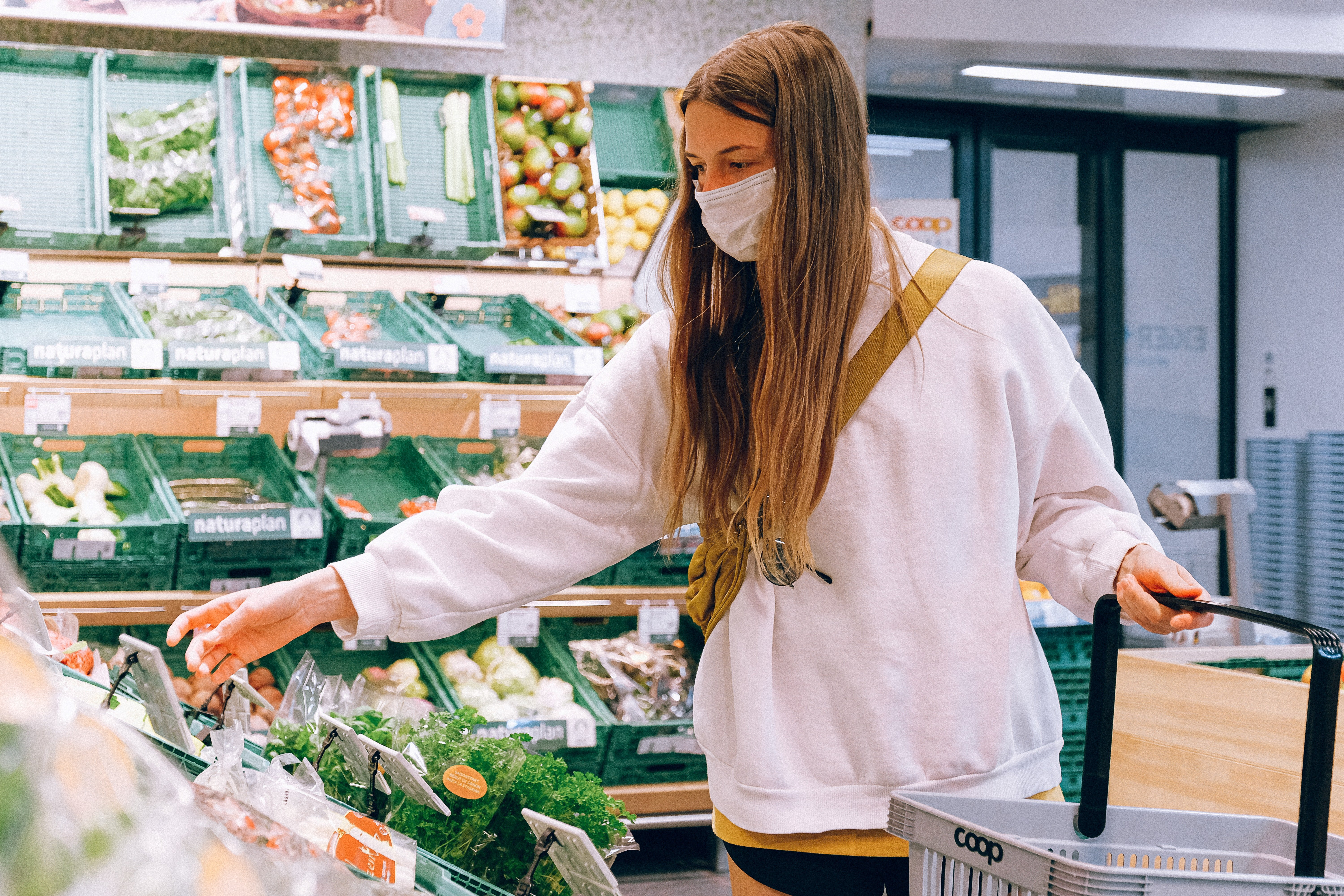 Image of a woman shopping while wearing a facemask | Source: Pexels/ Anna Shvets