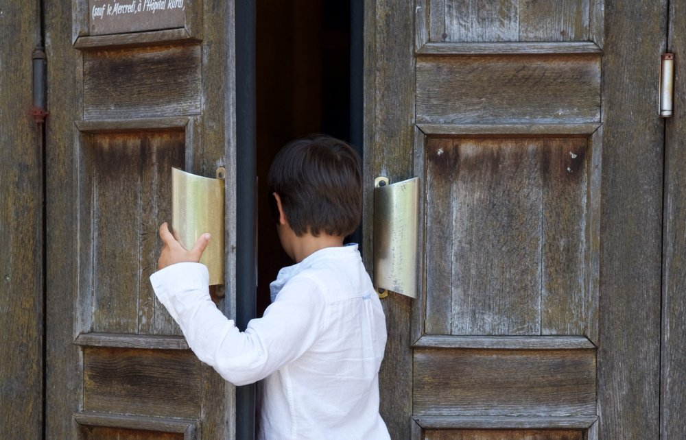 A little boy entering a church.| Photo: Shutterstock.