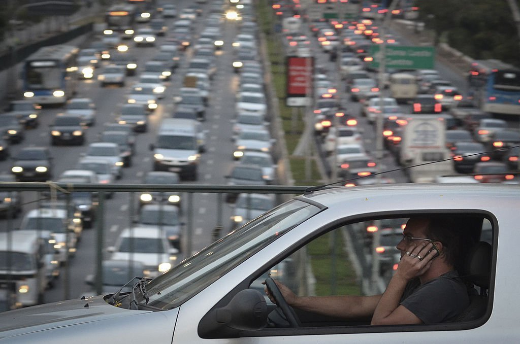 A man talks on his cellphone while driving on a highway on September 20, 2013 | Photo: Getty Images