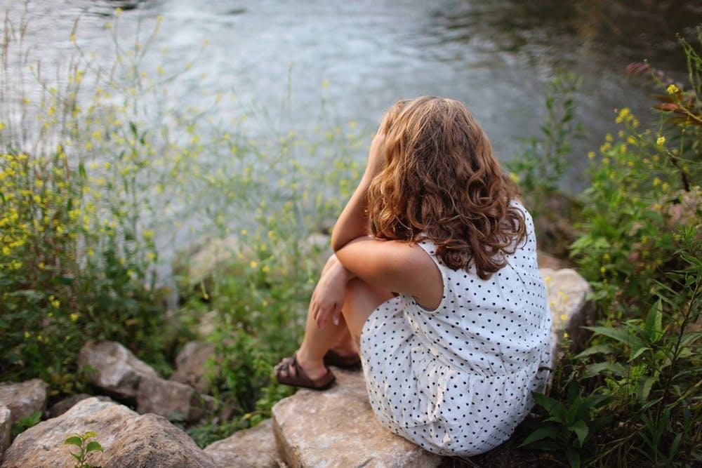 Femme assise au bord du lac | Photo: Pexels