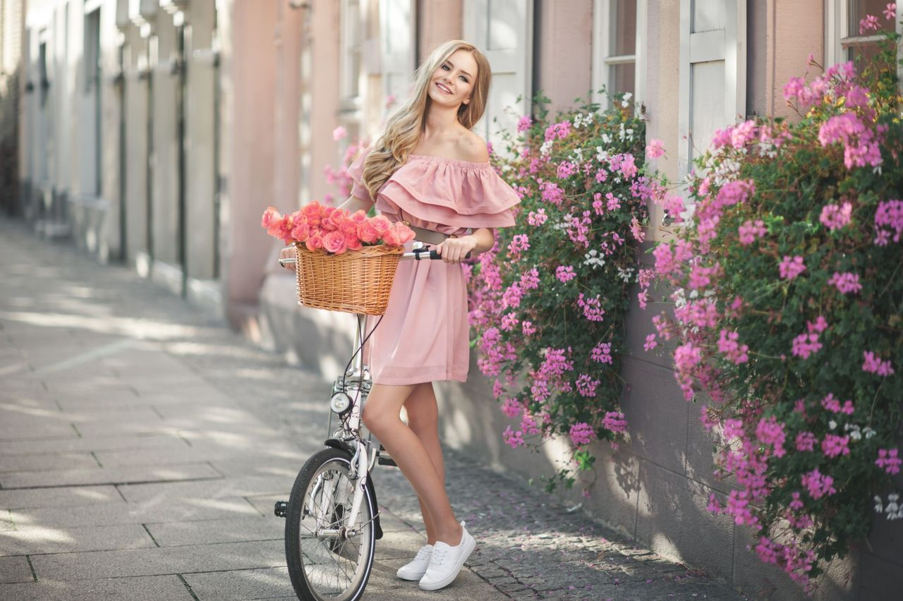A happy woman poses with her bike. | Source: Shutterstock