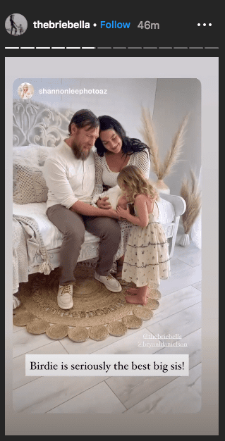 Photo of Brie and Bryan sitting on a white couch, holding Buddy on Brie's Instagram stories | Photo: Instagram /  thebriebella