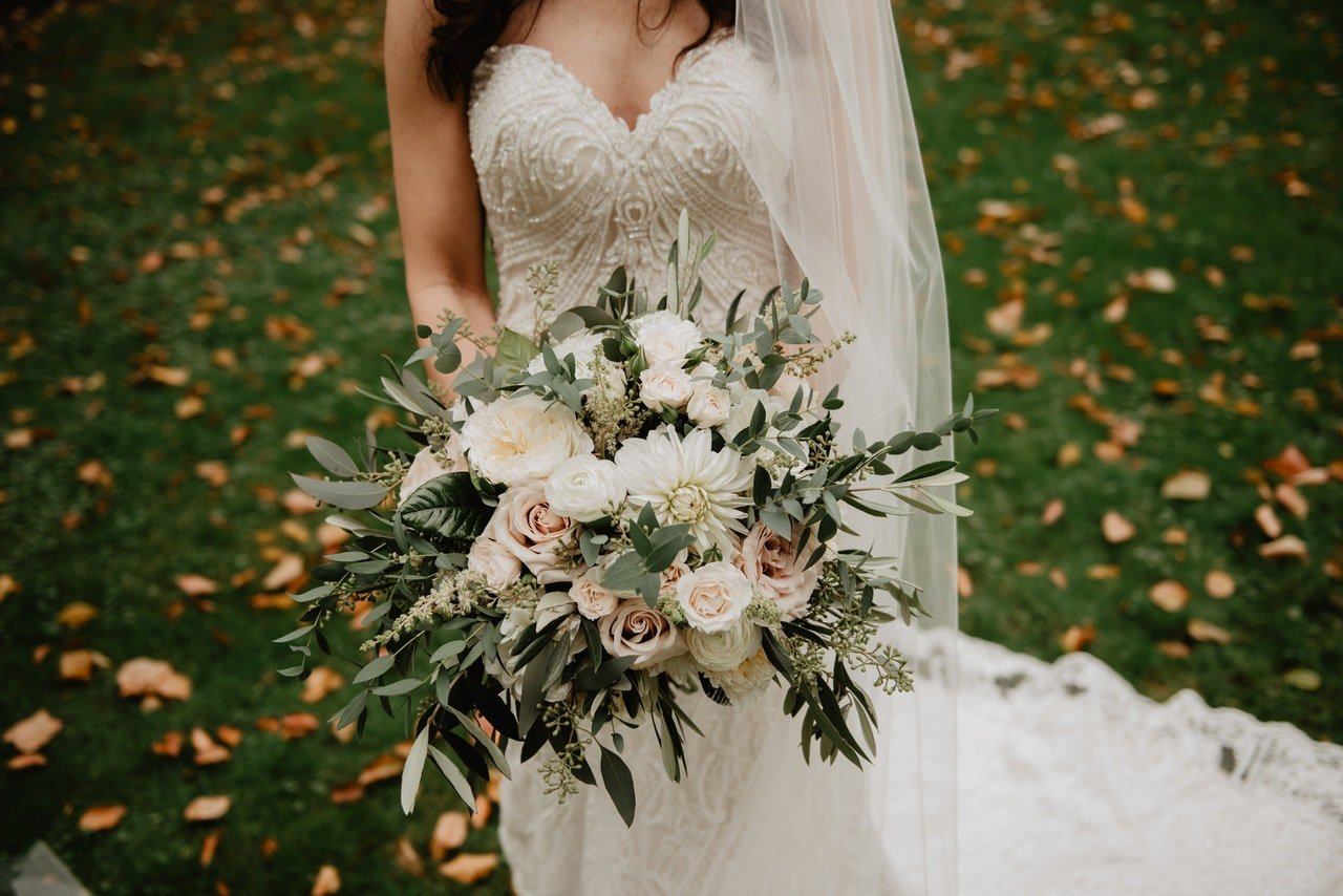 Woman in wedding gown with flower bouquet   Source: Pexels