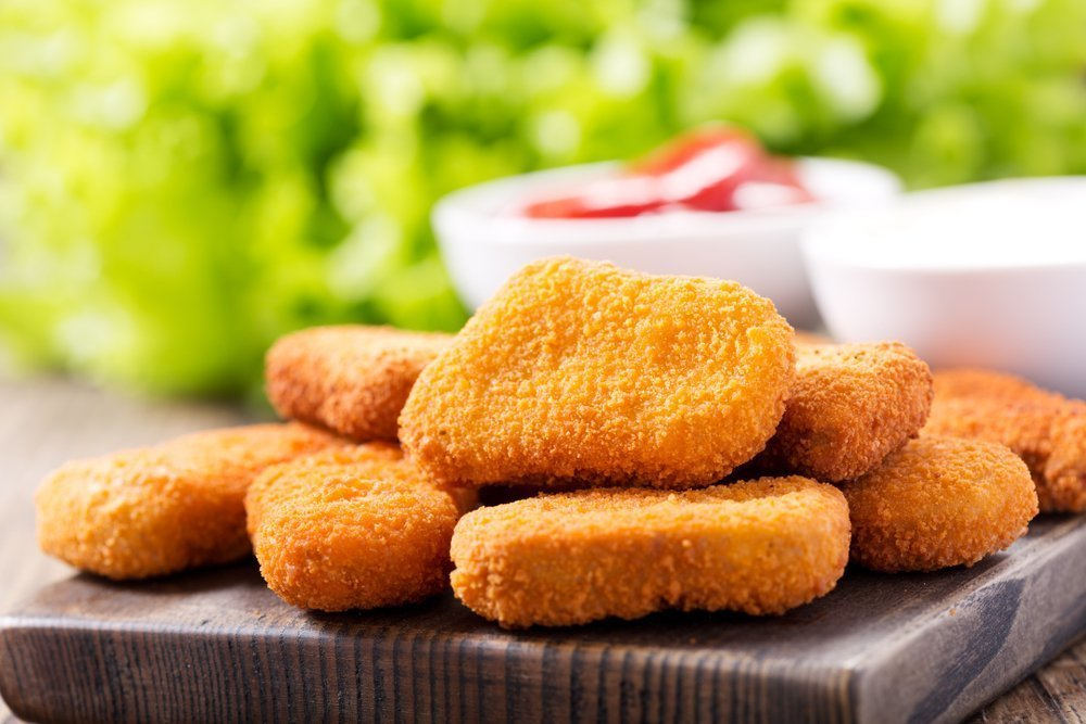 Chicken nuggets with sauces on wooden board. | Photo: Shutterstock