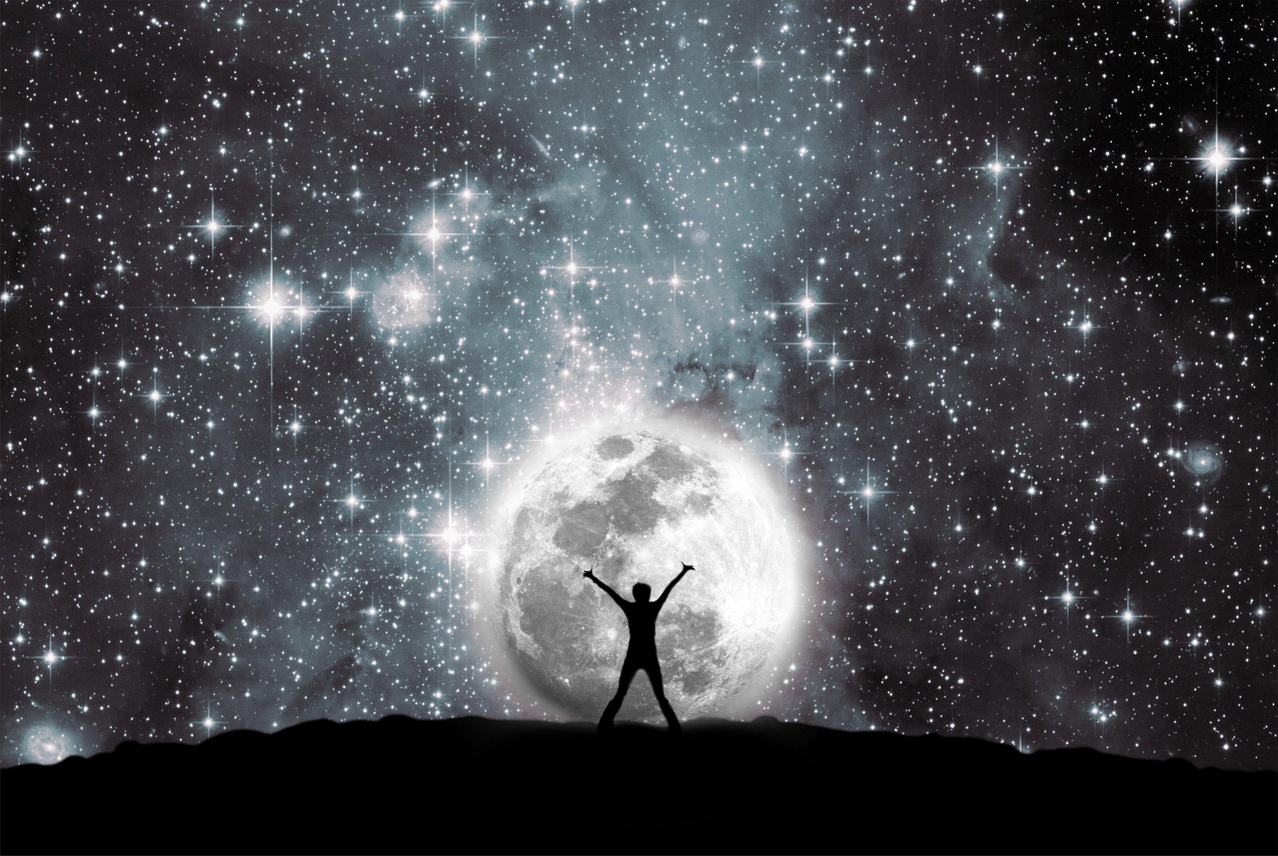 Silueta de hombre a contraluz contra la Luna y noche estrellada || Fuente: Shutterstock