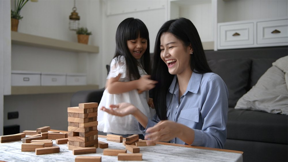 A mother and daughterplaying games together inthe house | Photo: Shutterstock/Sellwell