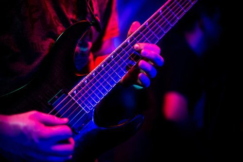 Guitarist playing with dimmed lighting. | Source: Shutterstock.