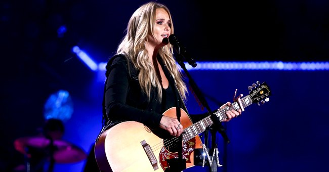 Miranda Lambert Poses in Knotted Shirt and Holds a Drink for a Stunning Window Shot