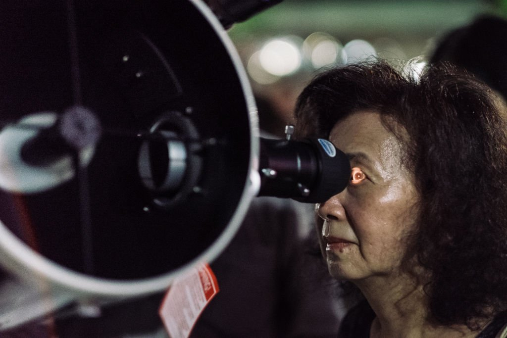A woman using telescopes to witness a rare lunar eclipse. | Photo:Getty Images