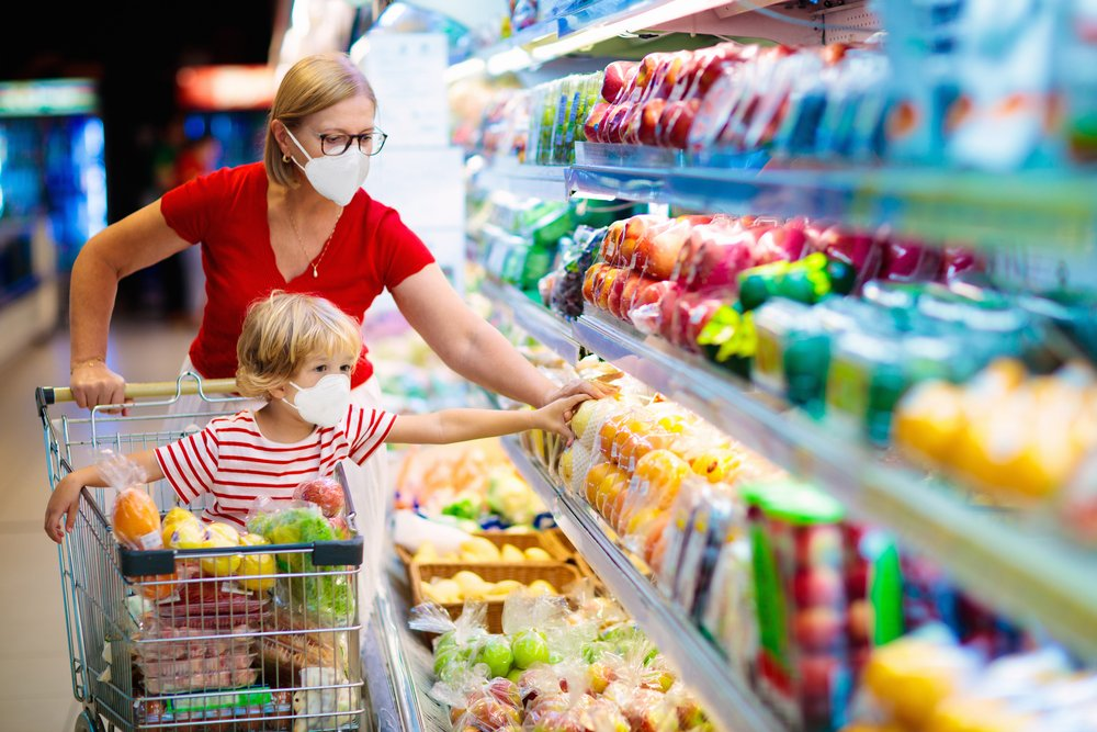 A mother and child wearing surgical face masks while shopping at a supermarket   Photo: Shutterstock/FamVeld