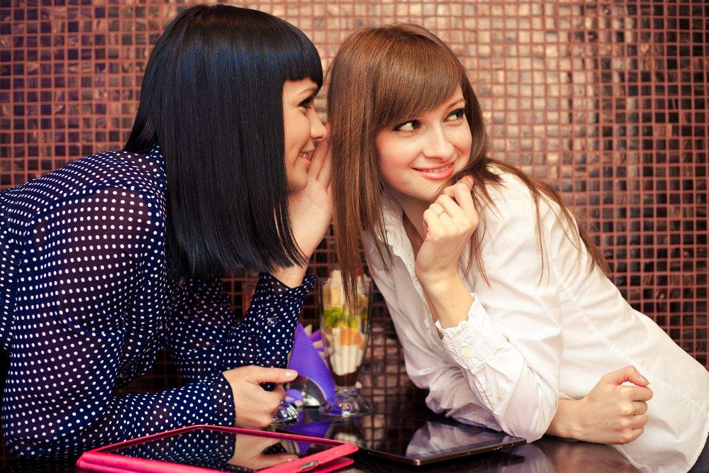Una mujer le susurra algo a su amiga en el oído. | Fuente: Shutterstock