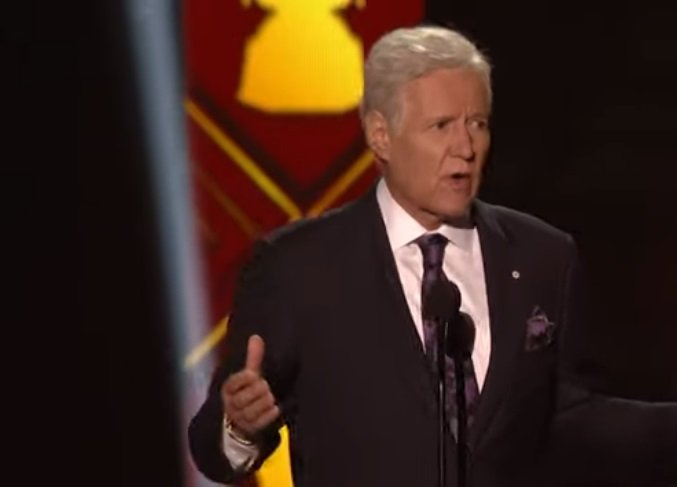 Alex Trebek presenting an award on stage at the NFL Awards.| Photo: YouTube/ NFL.