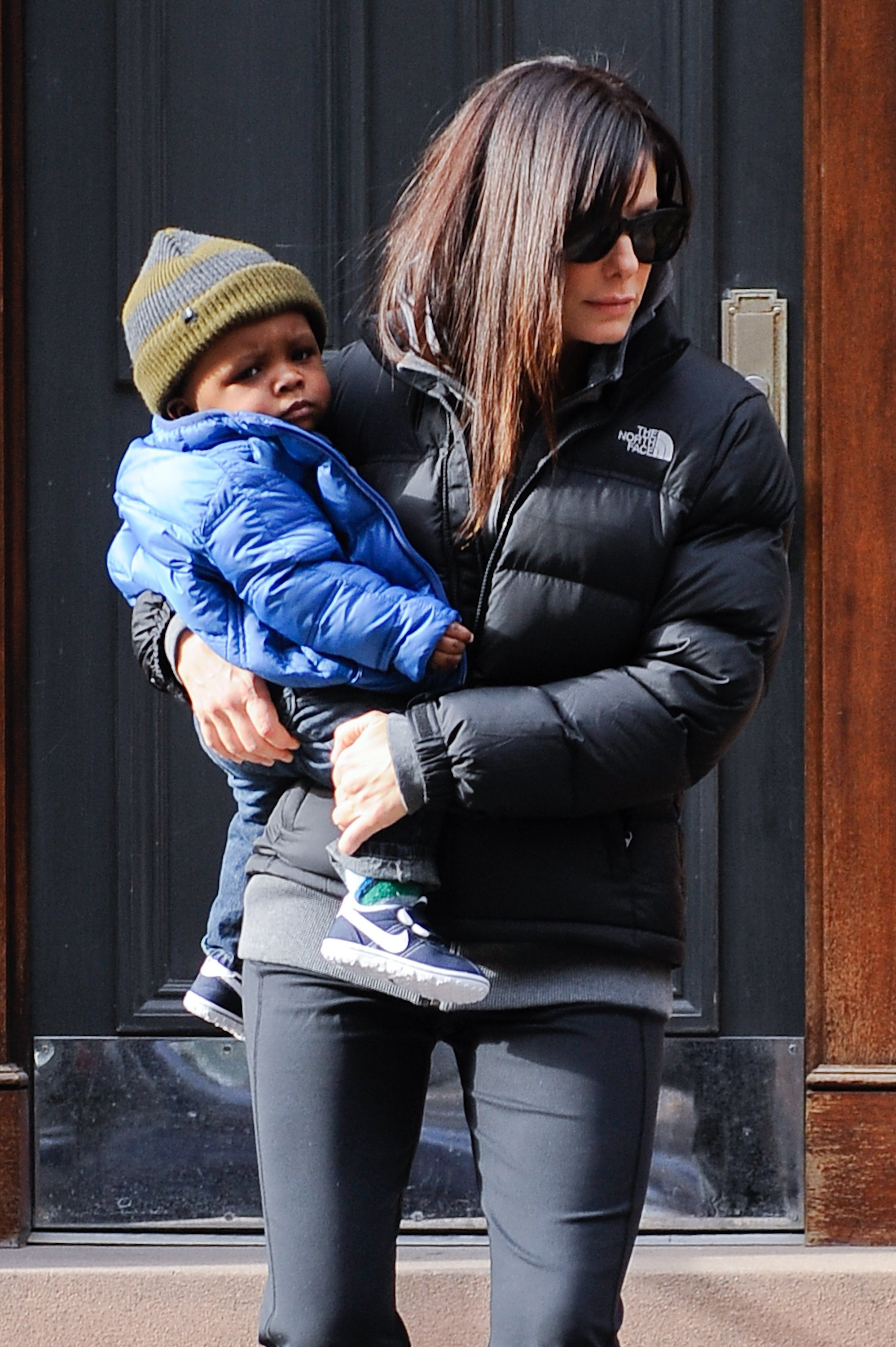 Sandra Bullock walking in public holding one of her children | Photo: Getty Images