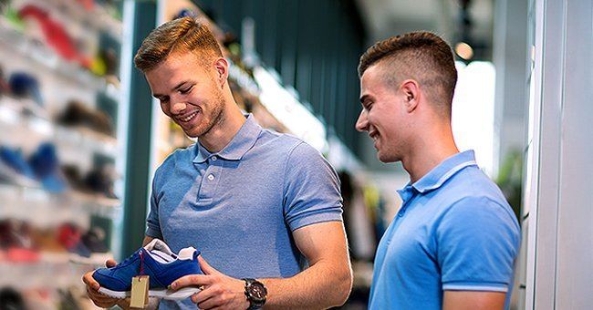 Two male friends at a store, smiling, and checking out sneakers | Photo: Shutterstock