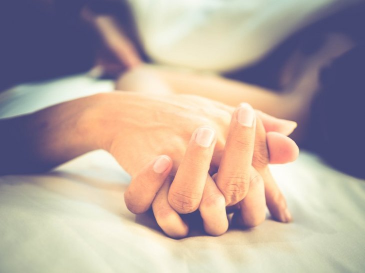 Un couple se tenant la main dans son lit. l Source: Shutterstock