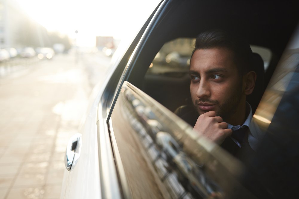 A photo of a man seating in the owner's corner of a luxurious car   Photo: Shutterstock